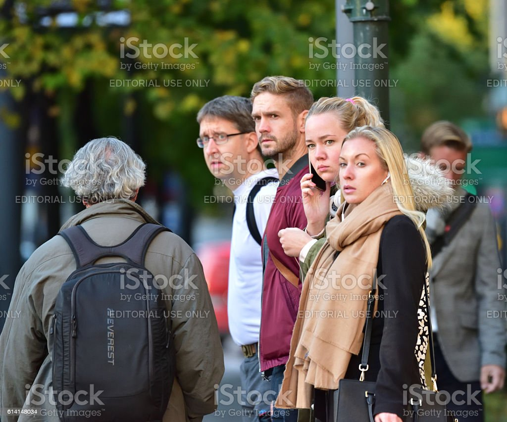 Women and men waiting at zebra crossing stock photo