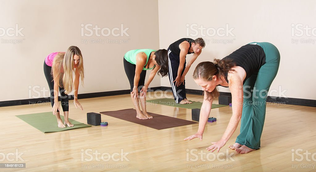Women and one man doing poses in a yoga class at a gym stock photo