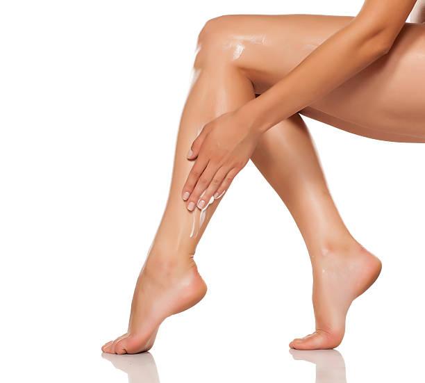 women applied the cream on her beautiful legs - foto de stock