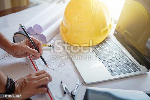 istock Women architect working on blueprint. 1129560192