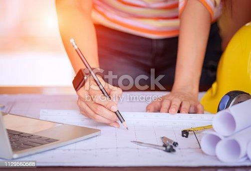 istock Women architect working on blueprint. 1129560568