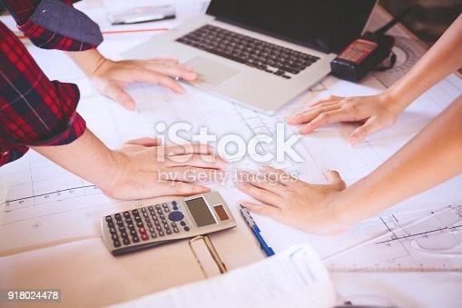 istock Women architect working on blueprint. 918024478