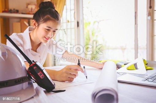istock Women architect working on blueprint. 918027116
