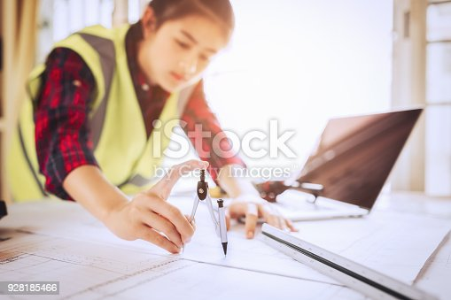 istock Women architect working on blueprint. 928185466