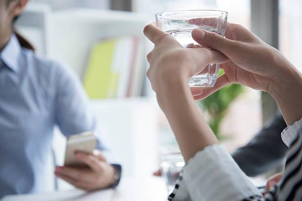 women are drinking water during a meeting - leitungswasser trinken stock-fotos und bilder