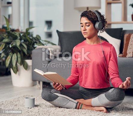 Full length shot of an attractive young woman sitting and listening to music while reading in her living room