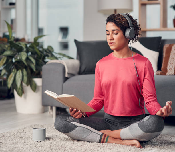 Women are great at multitasking Full length shot of an attractive young woman sitting and listening to music while reading in her living room mental wellbeing stock pictures, royalty-free photos & images