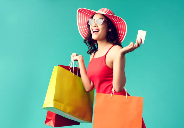 women are shopping in the summer she is using a credit card and enjoys shopping. - buying stock photos and pictures