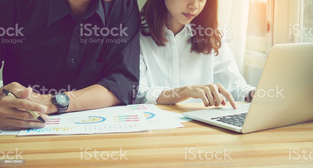 women are using the laptop on the table in the office, where men sit together is using the idea of work. Use graphics to advertise your computer screen. stock photo