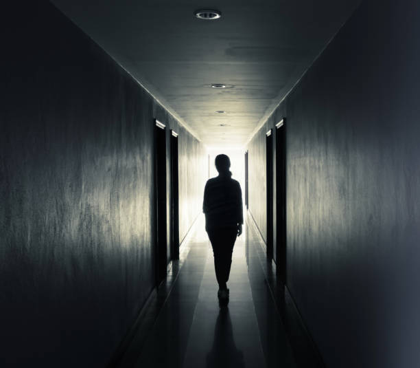 women are walking alone in the dark.light at the end of the tunnel concept - leaving stock photos and pictures