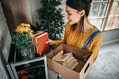 Young women unpacking in new rented apartment