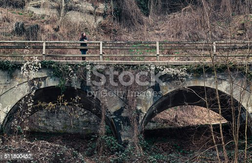 woman stands on an old viaduct and look down