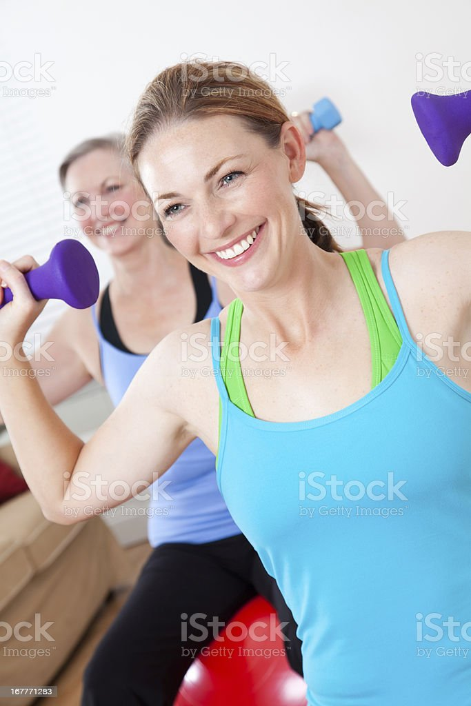 Women at home lifting weights while sitting on exercise ball royalty-free stock photo