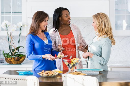 A group of three multi-racial women enjoying a party or luncheon, standing in the kitchen talking.  There is food on the table next to them, and one woman, wearing a blue dress, is holding a small plate.