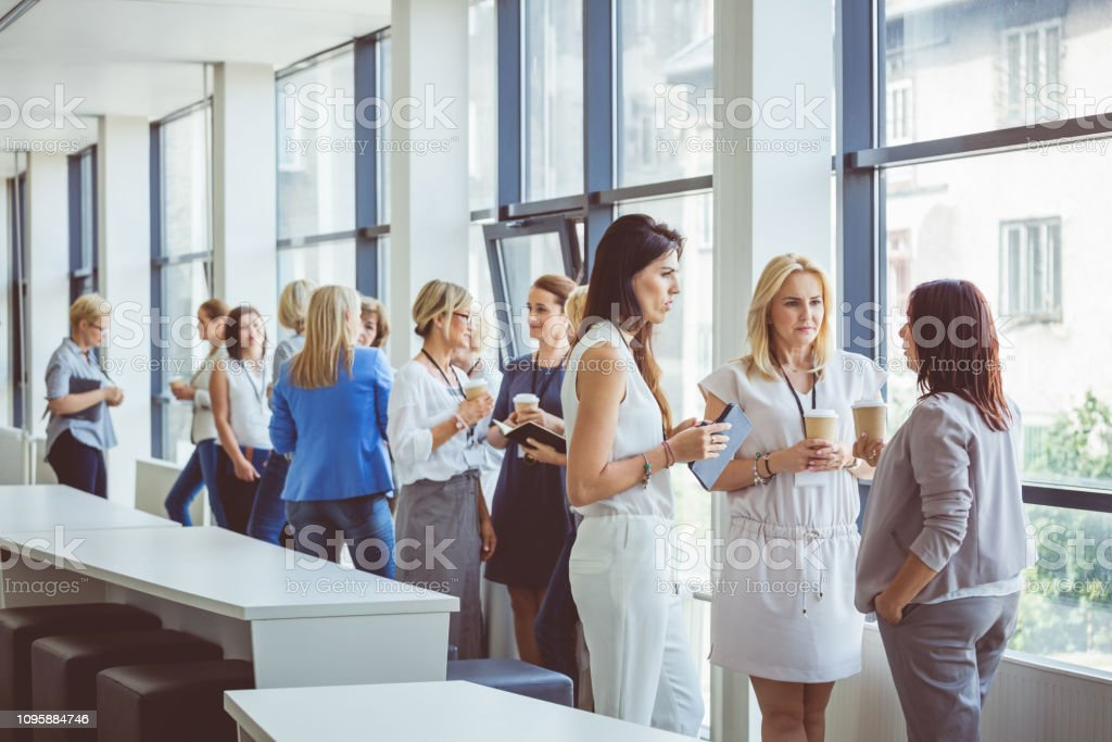 Women at seminar having a coffee break Group of women talking during a break. Women standing in office building lobby having coffee and talking. Adult Stock Photo