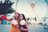 Two friends with cotton candy taking photos against the ferris wheel