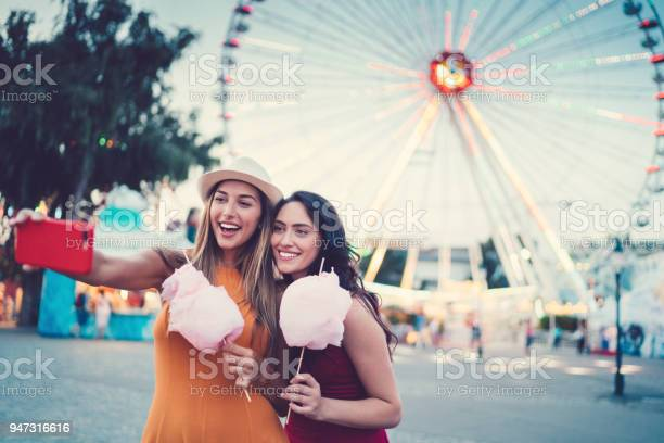 Women at the amusement park eating pink cotton candy and taking picture id947316616?b=1&k=6&m=947316616&s=612x612&h=w6f9eqkib48iqejqfh5xxubt9ddak7mrioq5ujggrdk=