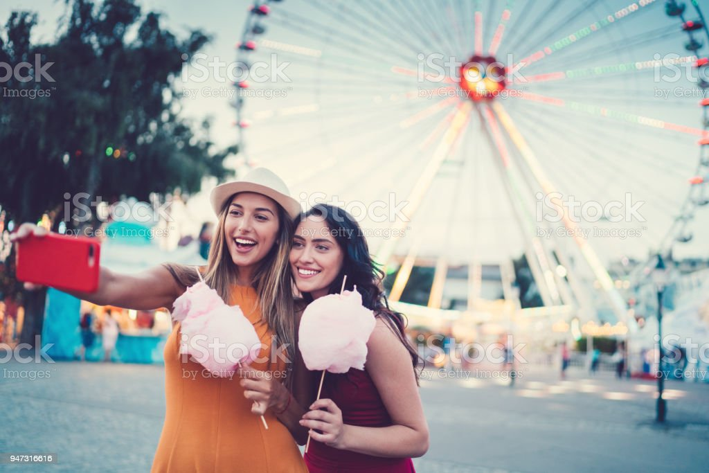 Women at the amusement park eating pink cotton candy and taking selfie/vlogging stock photo