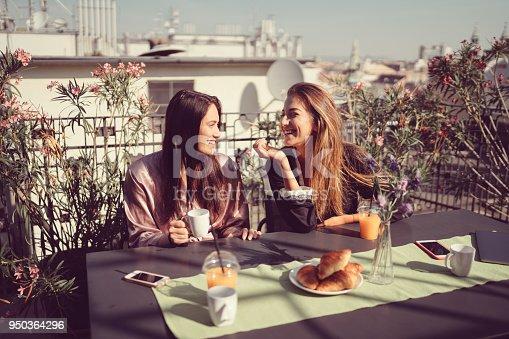 Two women enjoying breakfast at rooftop terrace
