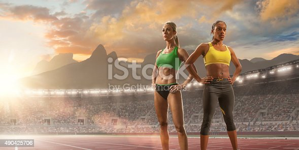 Two elite women track athletes of mixed ethnicity looking into the distance, and standing with hands on hips on an outdoor athletics track. They are in a generic Olympic stadium full of spectators under a colourful evening sunset in Rio de Janeiro, Brazil.  Sugarloaf Mountain and surrounding peaks are in the background.