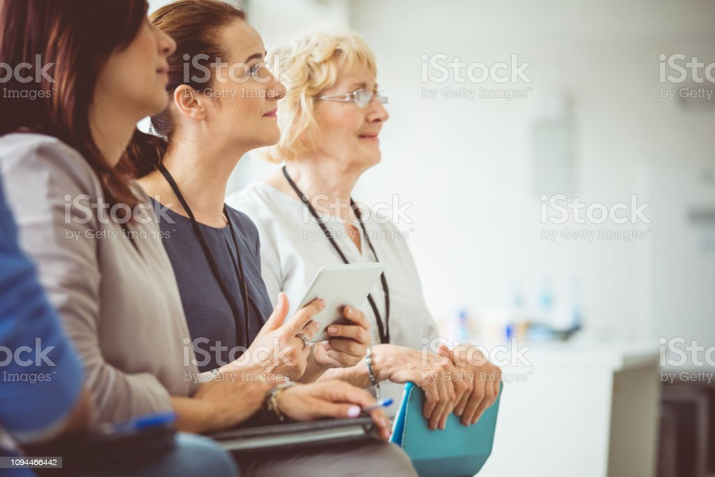 Women attending a seminar Group of business women listening to the speaker during training. Women attending a seminar. Adult Stock Photo