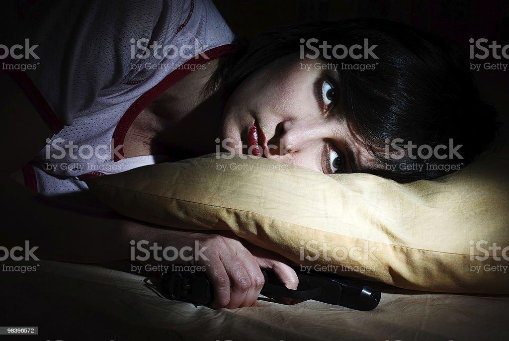 Donne si è alzata con Pistola sotto il cuscino foto stock royalty-free
