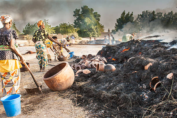 Women bake the clay pots in a big fire. stock photo