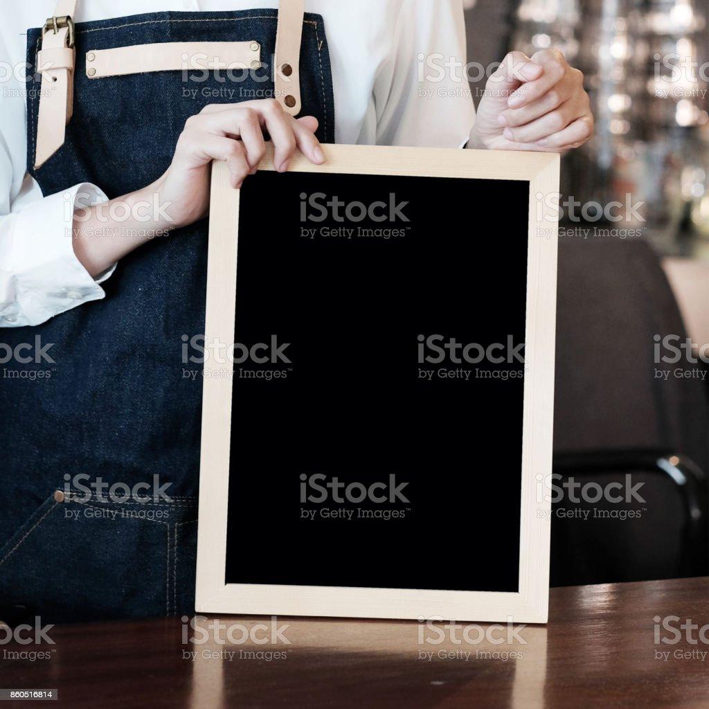 Frauen-Barista hält leere Tafel am Café Zähler Hintergrund, Menü-Hintergrund, Speisen und Getränke-Industrie-Konzept – Foto