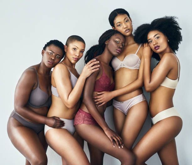 Women, beautiful in any shape and size Studio shot of a group of beautiful young women posing together in their underwear against a grey background lingerie stock pictures, royalty-free photos & images