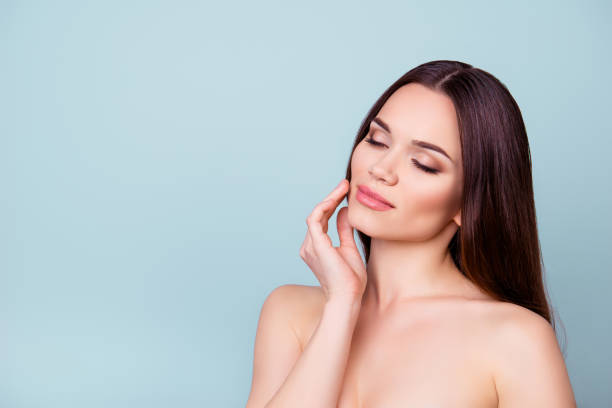 Women beauty and health, wellbeing concept. Young pretty brunette lady is touching gently her attractive healthy smooth skin stock photo