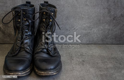 Pair of black leather retro shoes on grey background with copy space.