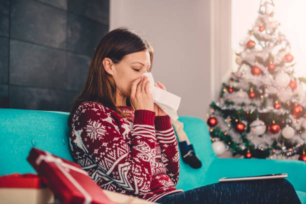 Women blowing her nose Women sitting on blue sofa by the christmas tree and blowing her nose human parainfluenza virus stock pictures, royalty-free photos & images