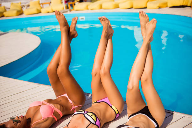 Women body care, pedicure, epilation, beauty, health concept. Close up cropped shot of long female legs of three multi ethnic hot chics with perfect smooth soft skin, getting tanned at beach stock photo