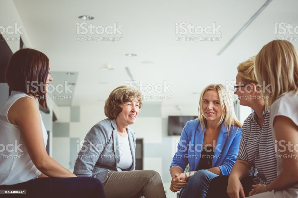 Women brainstorming during a training Group of women brainstorming during a training session. Mature woman talking with females trainees. Adult Stock Photo