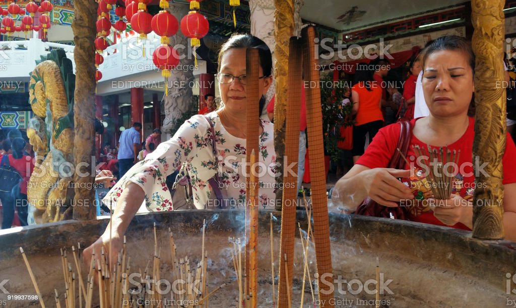 Women Burn Incense Sticks And Pray For Good Fortune During