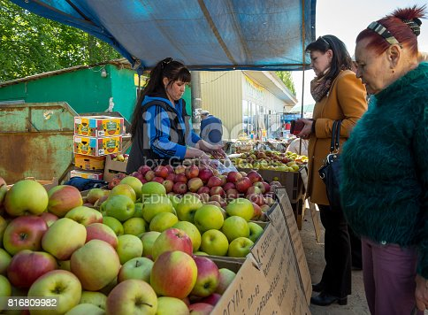 istock Women buy apples at the