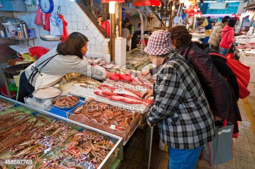 istock Women buying fresh fish from market stall Hong Kong 458597769