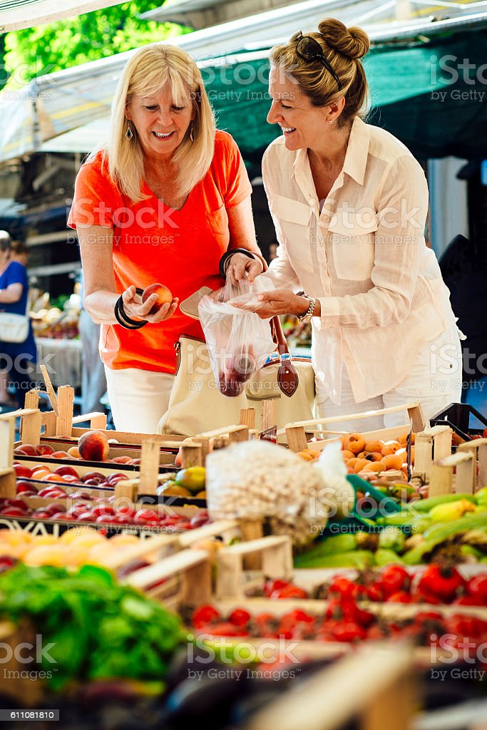 Women Buying Fruit from a Market Stall stock photo