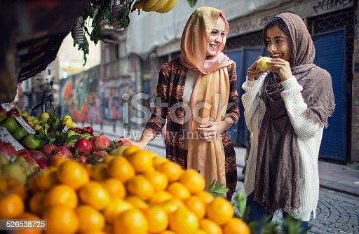 Two Turkish women buying fruits from the street vendor.