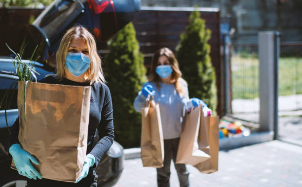 women buying groceries and back home. wearing protective mask and gloves - voluntário imagens e fotografias de stock