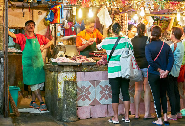 women buying meat at a stall in the market in baguio city - baguio city stock photos and pictures