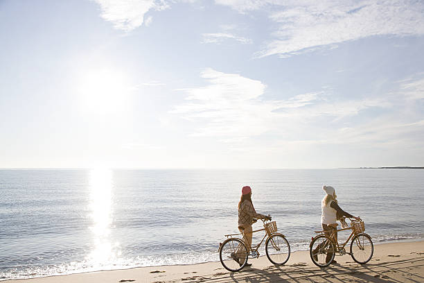 Women by the sea with bicycles  cape cod stock pictures, royalty-free photos & images