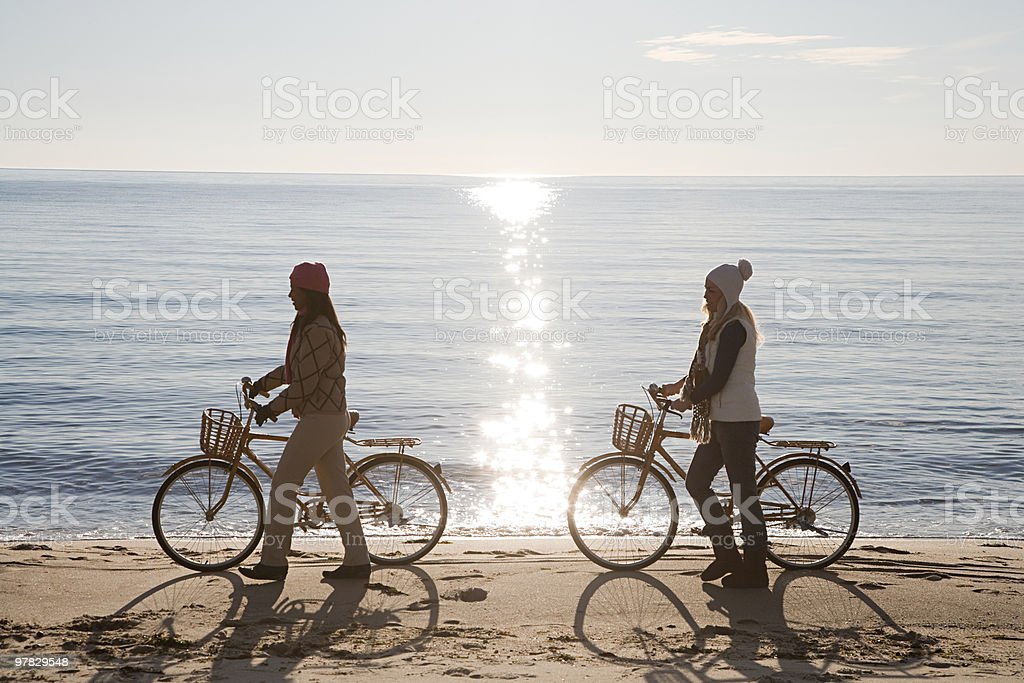 Women by the sea with bicycles stock photo