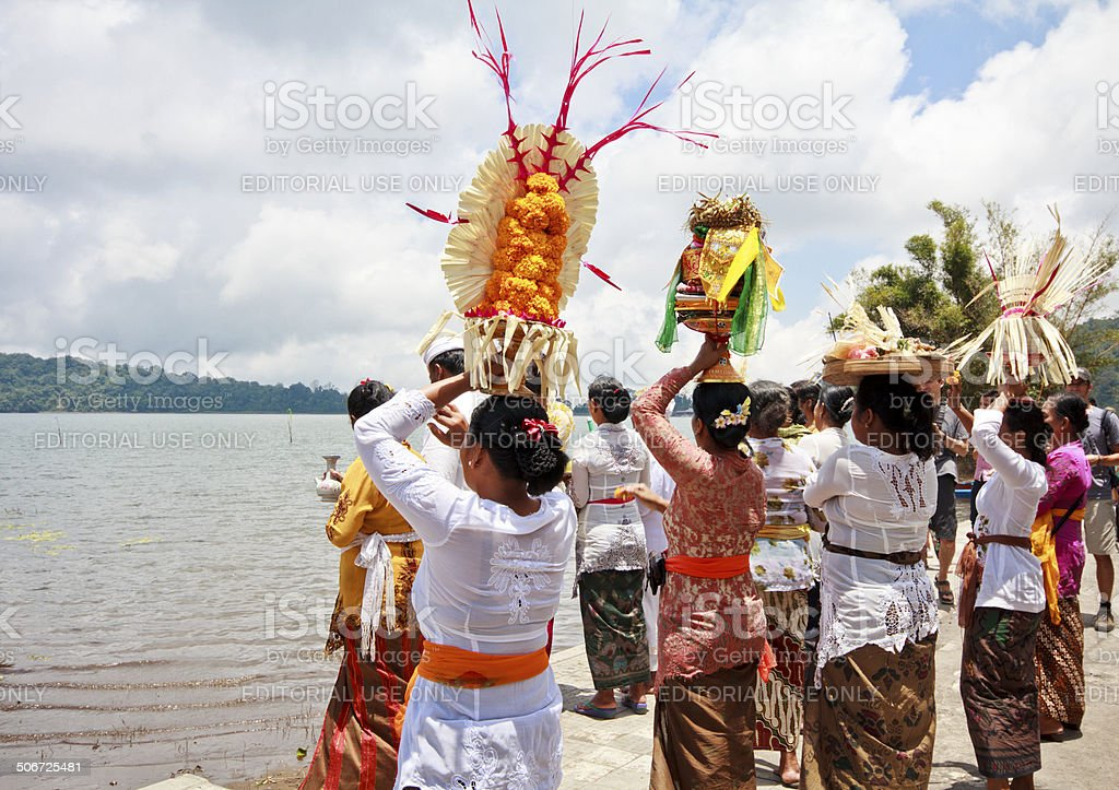 Women carrying offerings and praying in front of the lake royalty-free stock photo