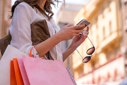 istock Women carrying shoppings bags and using smartphone 534203250