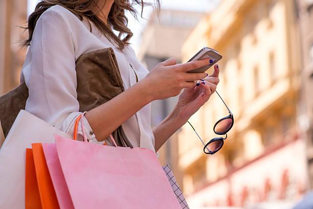 frauen tragen von shopping taschen und er ein smartphone benutzt - handytasche stock-fotos und bilder