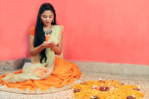 Close up Portrait of Indian women holding Diwali lamp or Diya and celebrating Diwali.