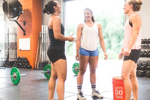istock Women chalk hands before a weightlifting cross training workout 597926866