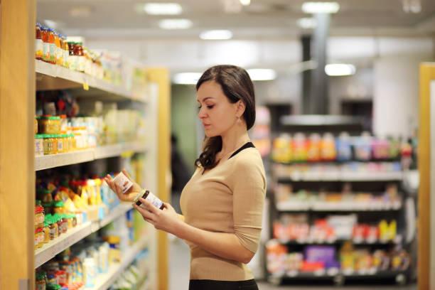 mujeres eligiendo lácteos en el supermercado. la lectura de información de producto - complemento vitamínico fotografías e imágenes de stock