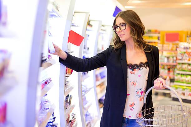 lipgloss frauen sie im einkaufszentrum - drogerie stock-fotos und bilder